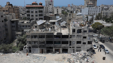 Palestinian bulldozer works to remove the debris atop the rubbles of a building destroyed by Israeli strikes, Gaza city, Gaza Strip, Palestinian Territory - 25 Jul 2021