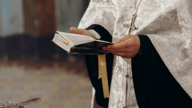 Priest reading holy bible in christian church during orthodox wedding ceremony, spiritual ritual concept