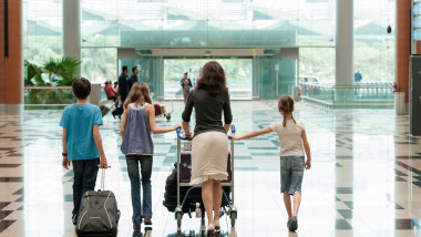 Family pushing luggage cart in airport, rear view