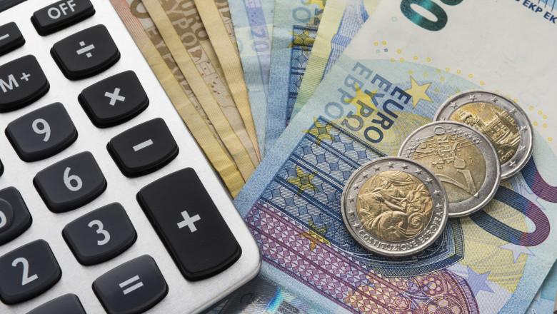 bancnote si monede euro langa un calculator