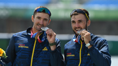(L-R)Silver medallists Romania's Marius Cozmiuc and Ciprian Tudosa pose on the podium following the men's pair final during the Tokyo 2020 Olympic Games