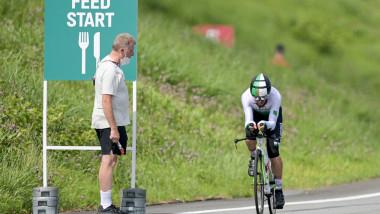 Bărbat cu mască privește spre un alt bărbat care merge pe bicicletă