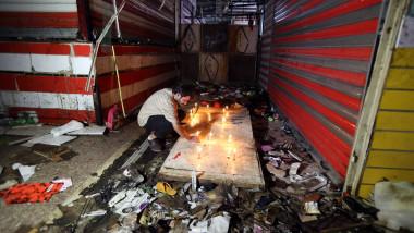 barbat aprinde lumanari in mijlocul distrugerilor din piata din sadr city bagdad, in urma atacaului sinucigas cu bomba