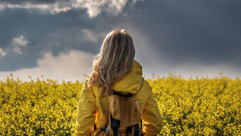 tanara cu haina galbena de ploaie intr-un camp cu fori galbene și cer noros