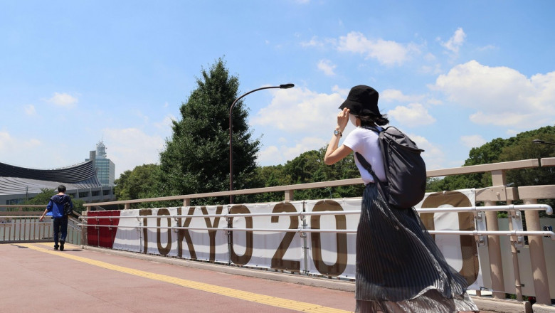 Tokyo, Japan. 19th July, 2021. A woman walks past the Tokyo 2020 Summer Olympic Games branding in Harajuku. Credit: SOPA Images Limited/Alamy Live News