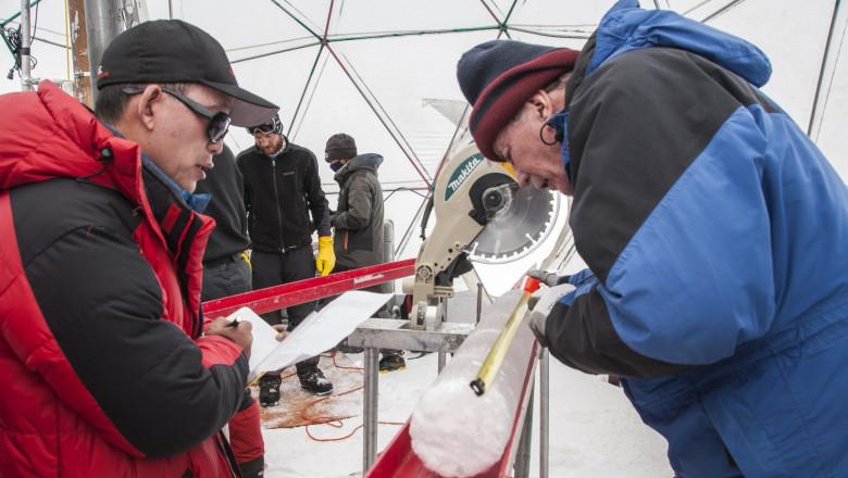 cercetatori examineaza un esantion cilindric de gheata din podisul tibet