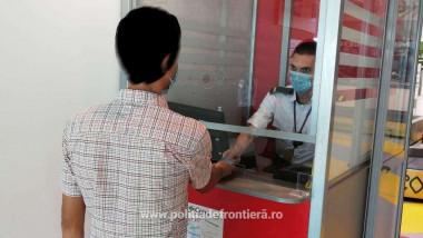 pasager la control pe aeroport pentru certificat covid si politist de frontiera la ghiseu