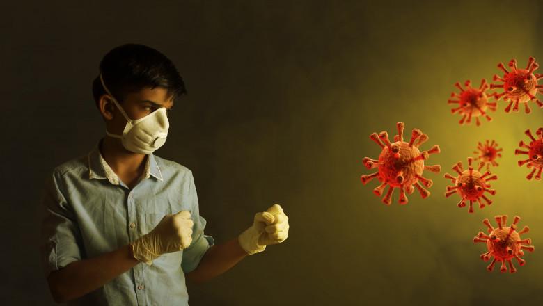 baiat cu masca si manusi care boxeaza cu coronavirusul