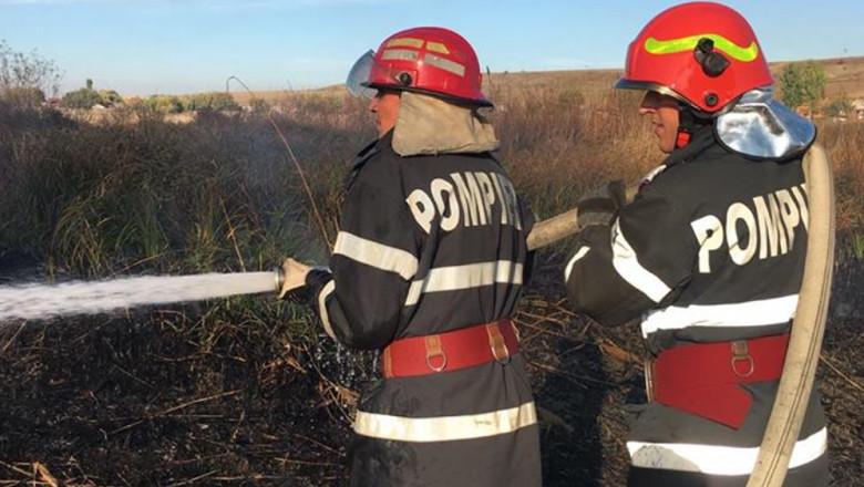Pompieri care intervin la un incendiu de vegetație uscată.