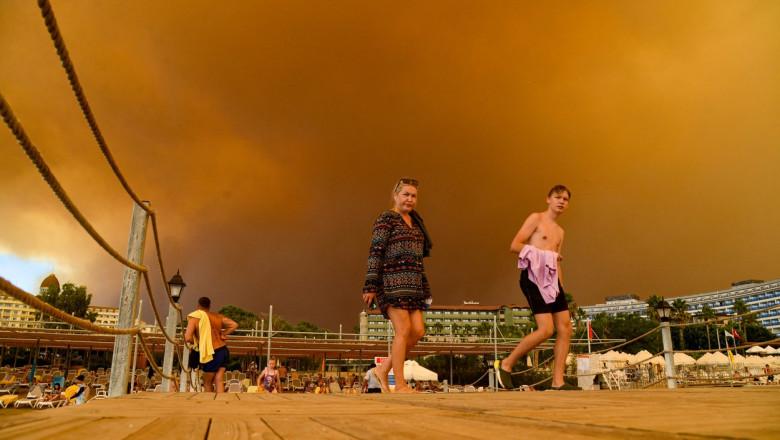 turisti avand in spate cerul rosu de la incendii si fum