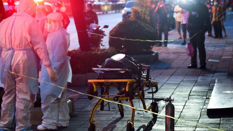 Oameni cu costume de protecție lângă o targă în mijlocul unei străzi