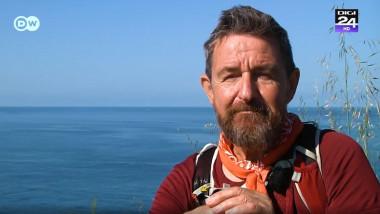 barbat cu barba in spatele caruia e marea