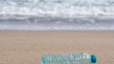 un pet de apă aruncat pe plajă