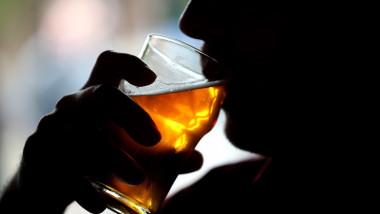 barbat care bea un pahar cu alcool