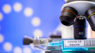 The objective lens of the microscope and the syringe for Covid-19 vaccine for coronavirus