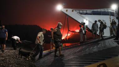 oameni evacuati din calea incendiilor urca pe feribot