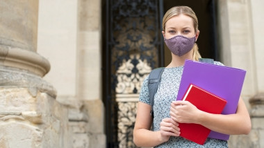 Portrait Of Female Student Standing Outside College Or University Building Wearing Face Mask During Covid-19 Pandemic