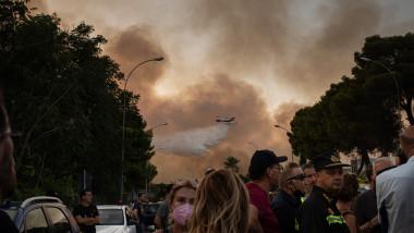 oameni stransi pe strada seara in timp ce in zare se vede un avion de stingere a incendiilor