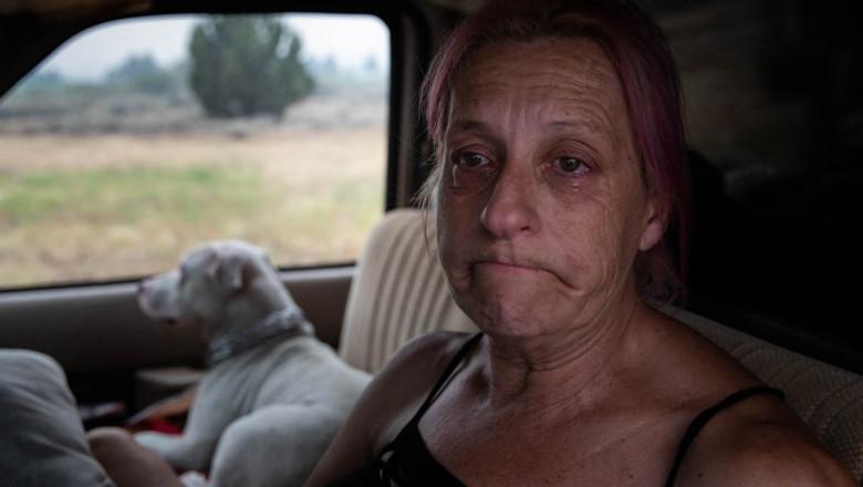 femie cu lacrimi in ochi intr-o masina cu un caine