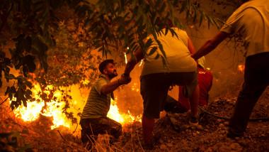 oameni care se ajuta in timp ce in spatele lor e un incendiu