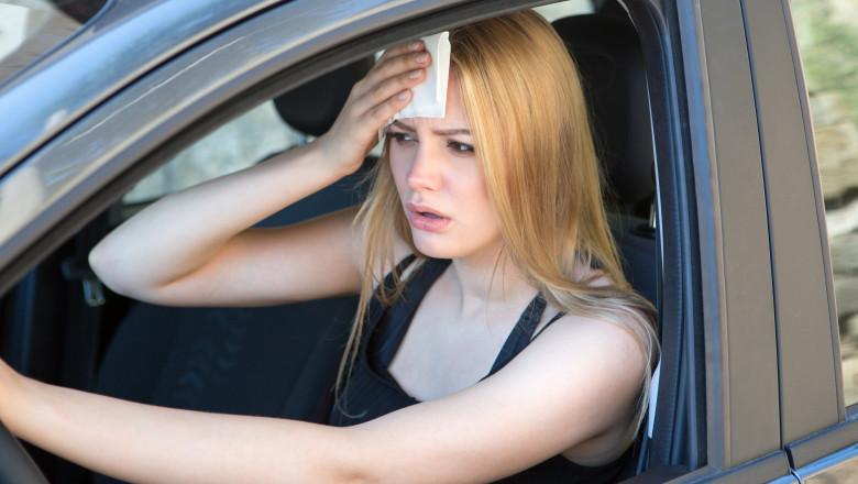 femeie tanara care se sterge pe frunte in timp ce se afla la volanul masinii