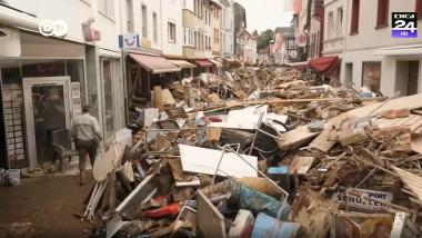 gramezi de resturi de lemn si alte deseuri ramase dupa inundatii pe o strada comerciala dintr-un oras german