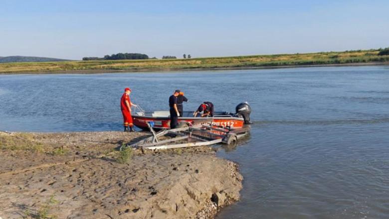 Pompieri cu barca la marginea unui râu.