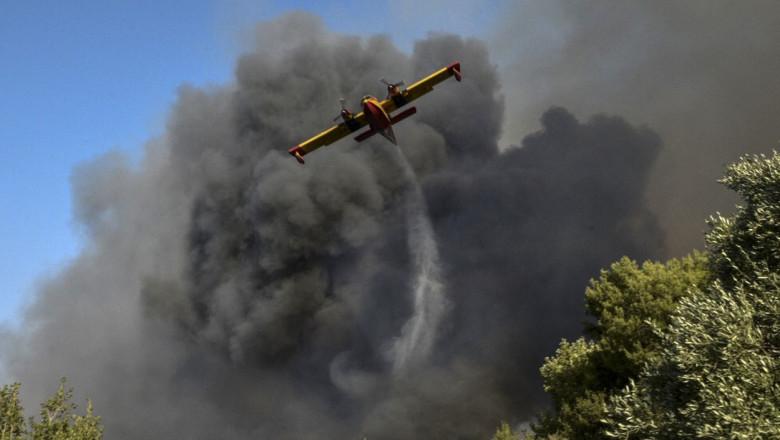 un avion de stingere a incendiilor zboara avand in spate o coloana groasa de fum negru