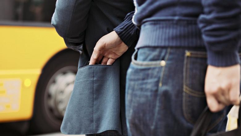 Un bărbat fură un portofel din buzunarul unei persoane.