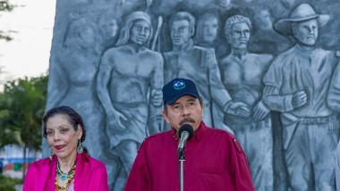 Bărbat și femeie la un microfon cu un monument în spate