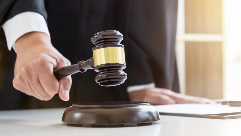 Un judecător bate cu ciocănelul în masă.