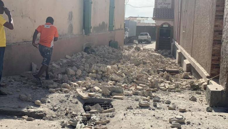 un barbat fuge pe o strada cu moloz in urma unui cutremur