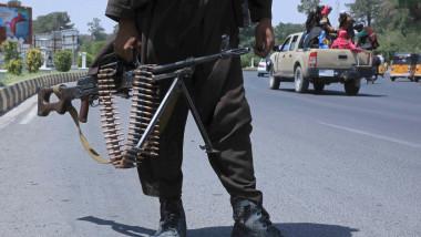 luptator taliban cu o arma in mana pe o sosea in timp ce in fundal se vede o masina pickup cu afgani in spate