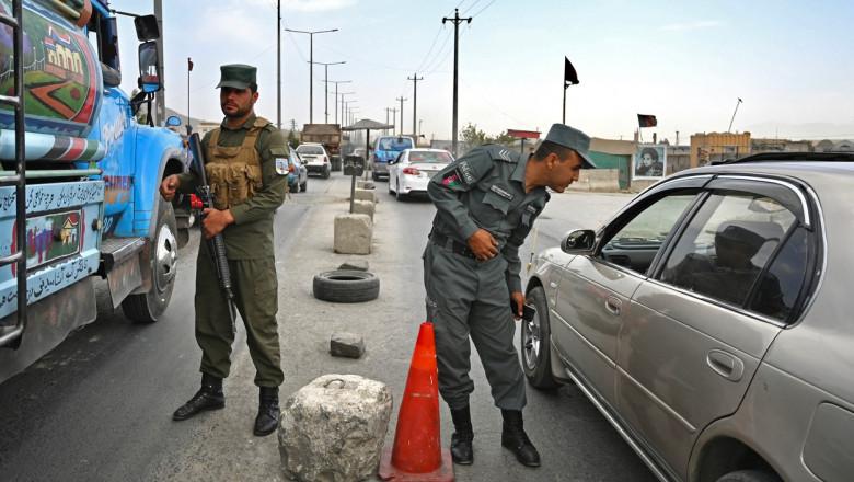 politisti afgani facand verificari la masini la un punct de control la intrare in kabul