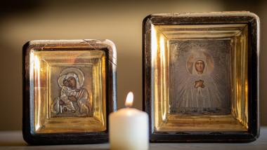 o candela care arde in fata unor icoane cu maica domnului