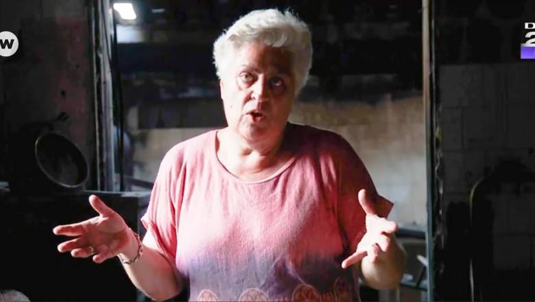 o femeie intr-o incapere arsa gesticuleaza si explică