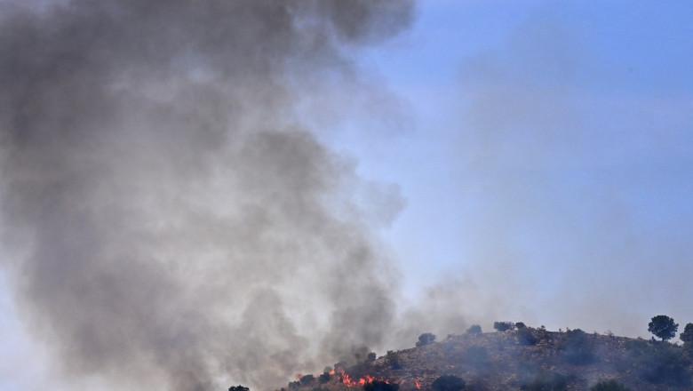 fum care se ridica de la un incendiu de vegetatie intr-o zona de deal