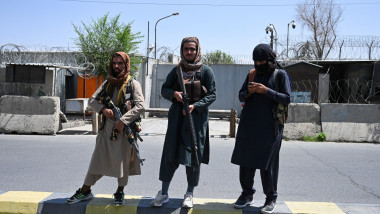 Taliban fighters stand guard along a street in Kabul on August 16, 2021