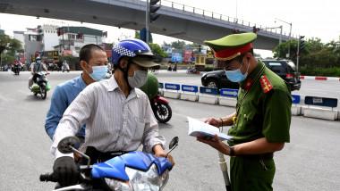 Un polițistul verifică documentele unor șoferi de scuter în timp ce guvernul vietnamez impune noi restricții pandemice pentru a opri răspândirea virusului SARS-CoV-2