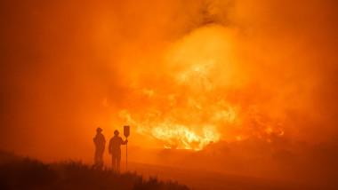 doi pompieri stau si privesc flacari uriase ale unui incendiu de vegetatie