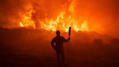 pompier cu loptata priveste la flacarile unui incendiu de vegetație