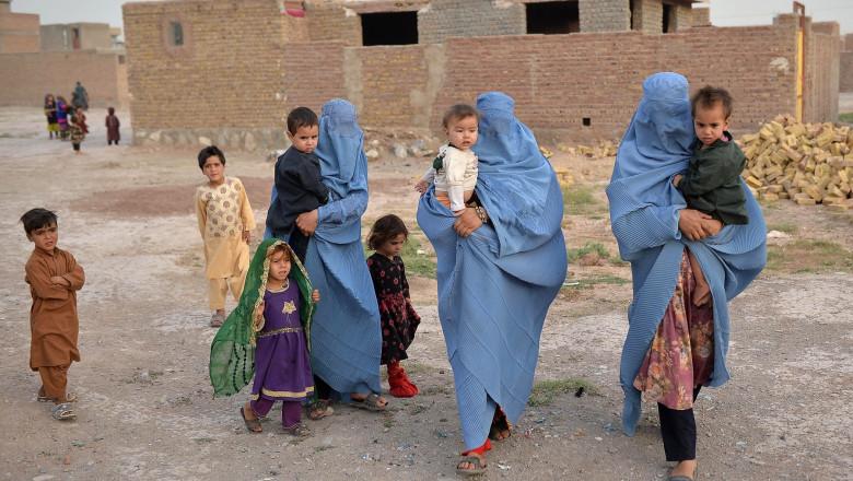 Femei dintr-o familie afgană strămutată din cauza conflictului dintre talibani și forțele de securitate ale guvernului care poartă burqa.