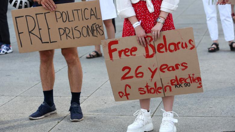 Oameni cu pancarte cu mesaje la un protest anti-Lukașenko organizat în Germania, după alegerile prezidențiale din Belarus din 2020