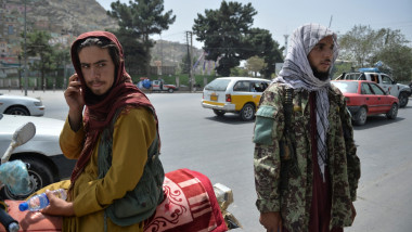 Taliban fighters stand along a road in Kabul on August 18, 2021