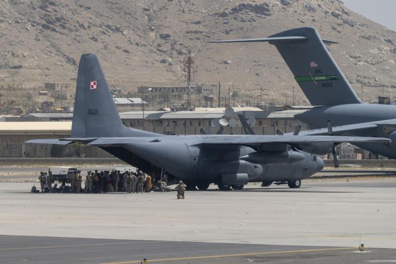 Oameni intrând într-un avion militar pe aeroportul din Kabul în timpul evacuării personalului militar și diplomatic după căderea țării în mâinile talibanilor