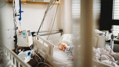 Copil mic pe un pat de spital