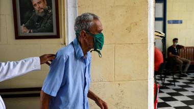 Bărbat în vârst merge pe un coridor cu portretrul dictatorului cubanez Fidel Castro