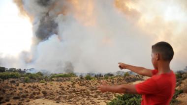 Un copil cu tricou roșu arată spre un nor înalt de fum și abur