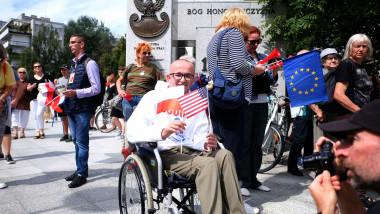 Protestatari în Polonia. În centru, un bărbat în scaun cu rotile care ține în mâini un steag al SUA