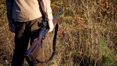 persoană ţine o armă de vânătoare